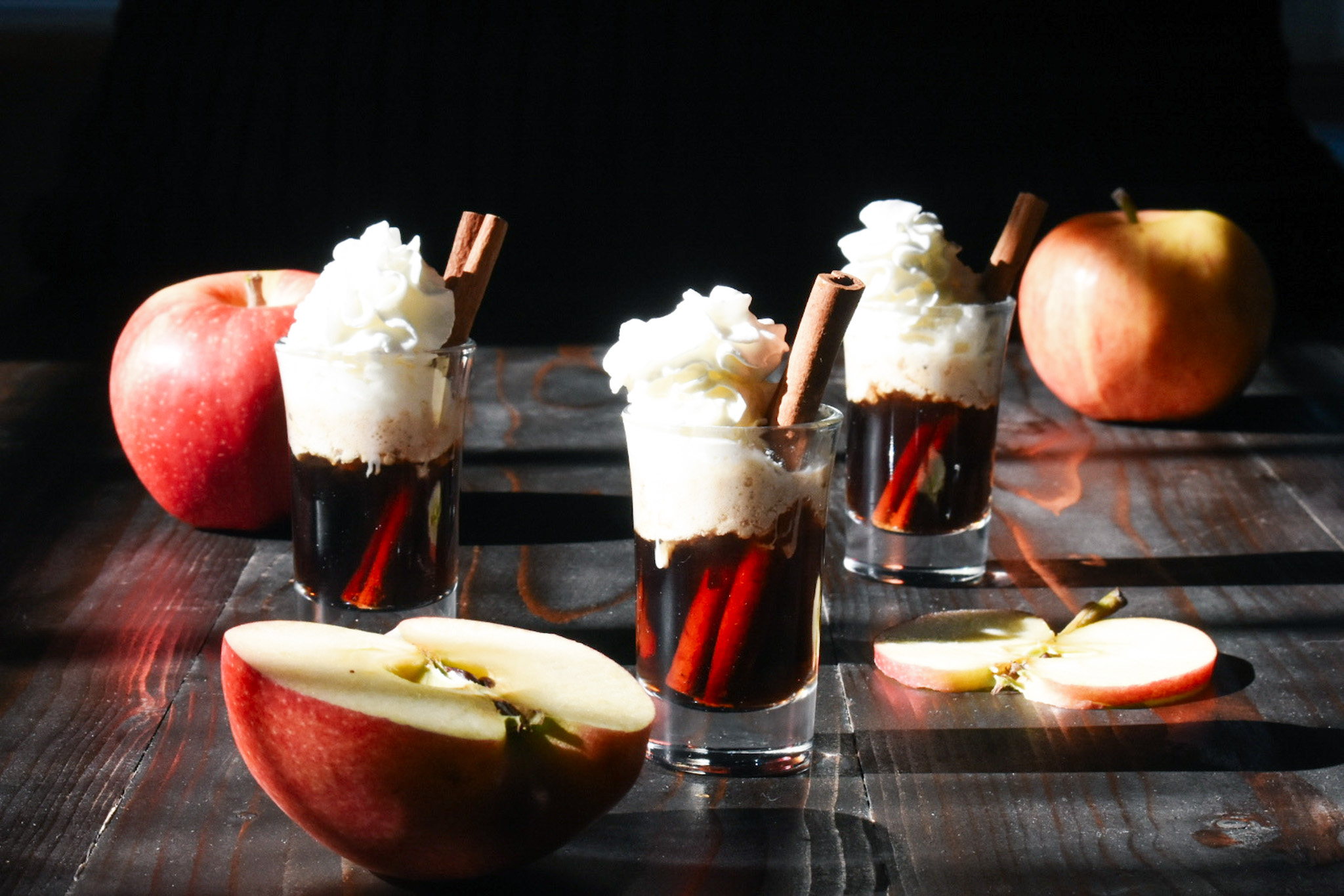 apple shots with whipped cream and cinnamon stick and apples